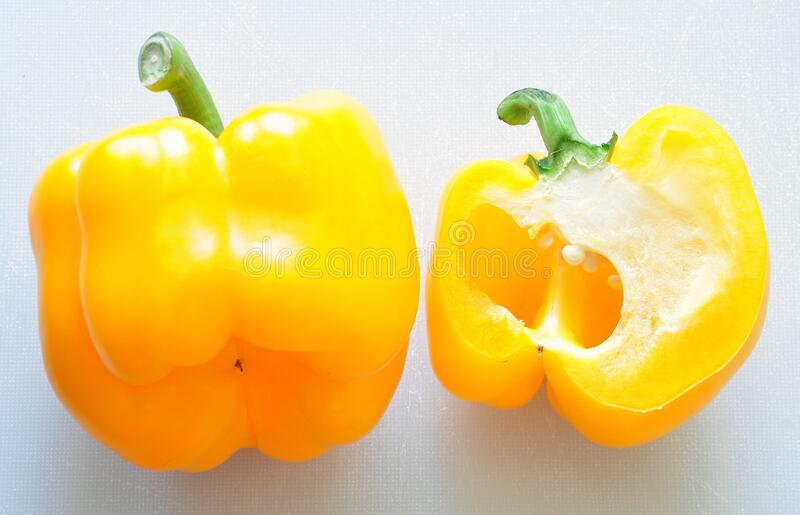 Whole and halved Yellow Capsicum on chopping board background royalty free stock photography