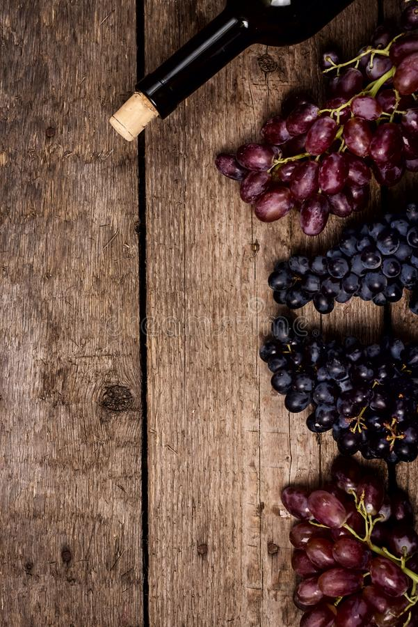 Top view Wine Background Wine Bottles Black and Pink Ripe Grapes on Wooden Background Vertical Copy Space royalty free stock photos