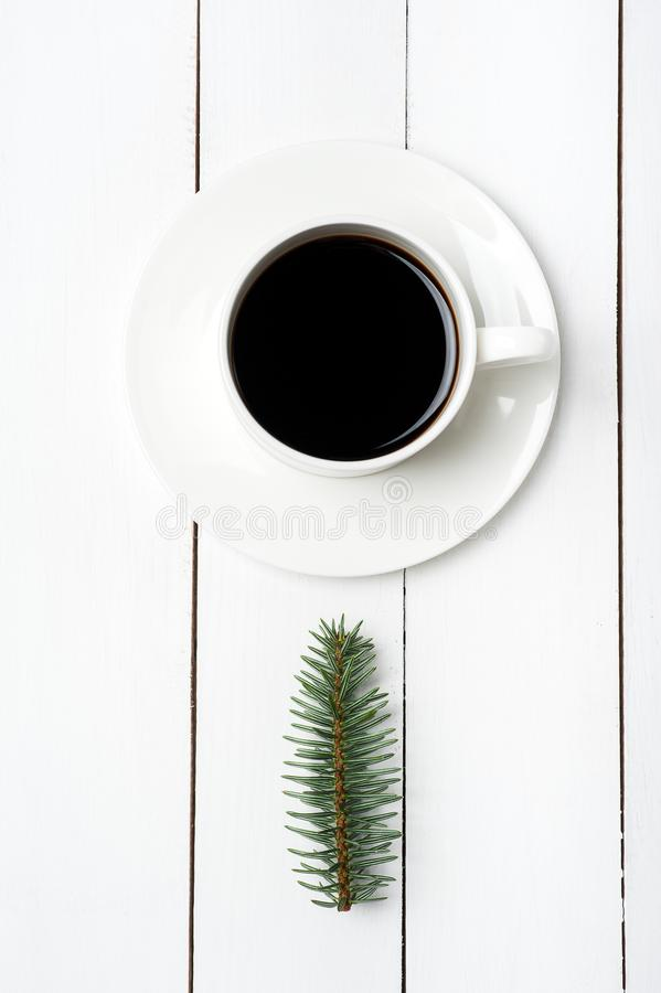 Top view of winter composition of cup of coffee and fir tree branch on white wood background. Christmas morning in Scandinavian royalty free stock photo