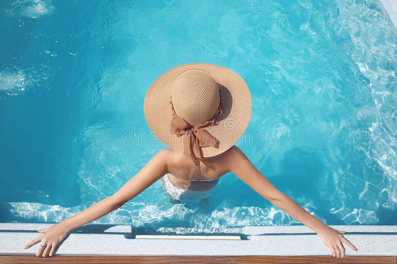 Top view of Woman in beach hat enjoying in swimming pool on luxury tropical resort. Exotic Paradise. Travel, Tourism and Vacation stock photos