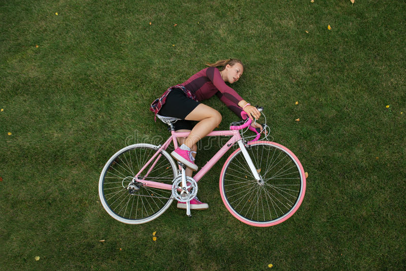 Top view of woman with bicycle on the grass. Active woman with bicycle on the green grass. Top view. Active lifestyle royalty free stock photos
