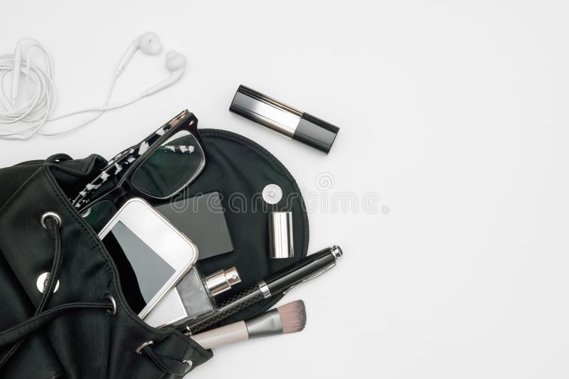 Top view of woman black bag open out with accessories smartphone, perfume, pens, cosmetics, earphone and glasses on white. Background stock photos