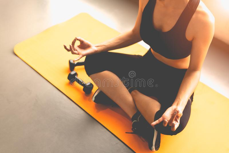 Top view woman doing finger trigger yoga or pay obeisance in fitness workouts training gym center.  Lifestyle sport woman sitting. On mat with sport equipment royalty free stock photos