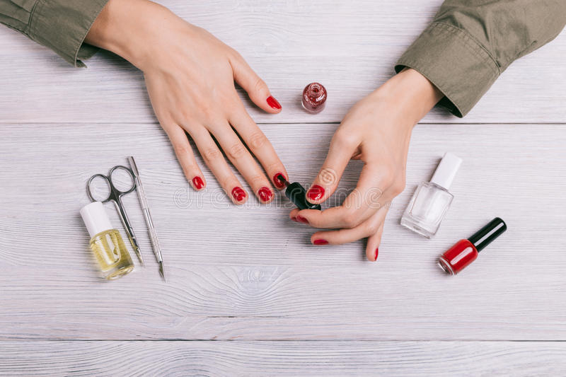 Top view of a woman doing a manicure and paint nails with red la. Cquer stock images