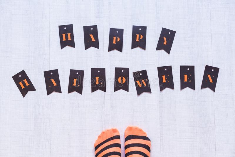 Top view of a woman feet with a happy halloween letters on the floor. Woman wearing a black and orange stripes tights. Concept. Indoors and lifestyle, candies stock images