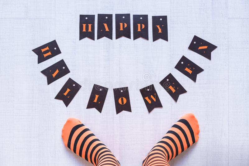 Top view of a woman feet with a happy halloween letters on the floor. Woman wearing a black and orange stripes tights. Concept. Indoors and lifestyle, candies royalty free stock photography