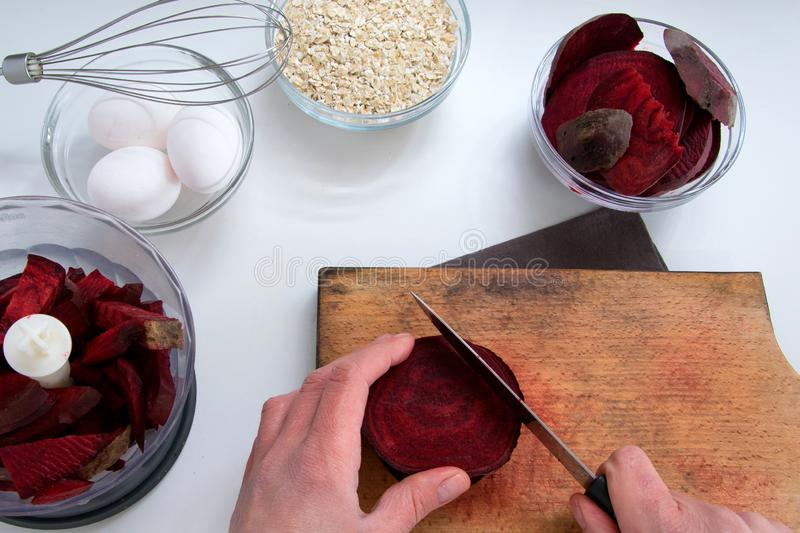 Top view of woman hands cooking healthy dessert with red beet roots, oats and eggs. Top view of woman hands cooking healthy dessert with red beet roots, oats and royalty free stock photography