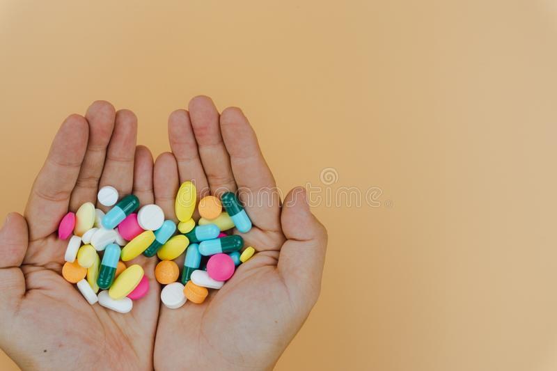 Top view of woman hands holding assorted pharmaceutical medicine pills on yellow background. Hard working and stressful business stock photo