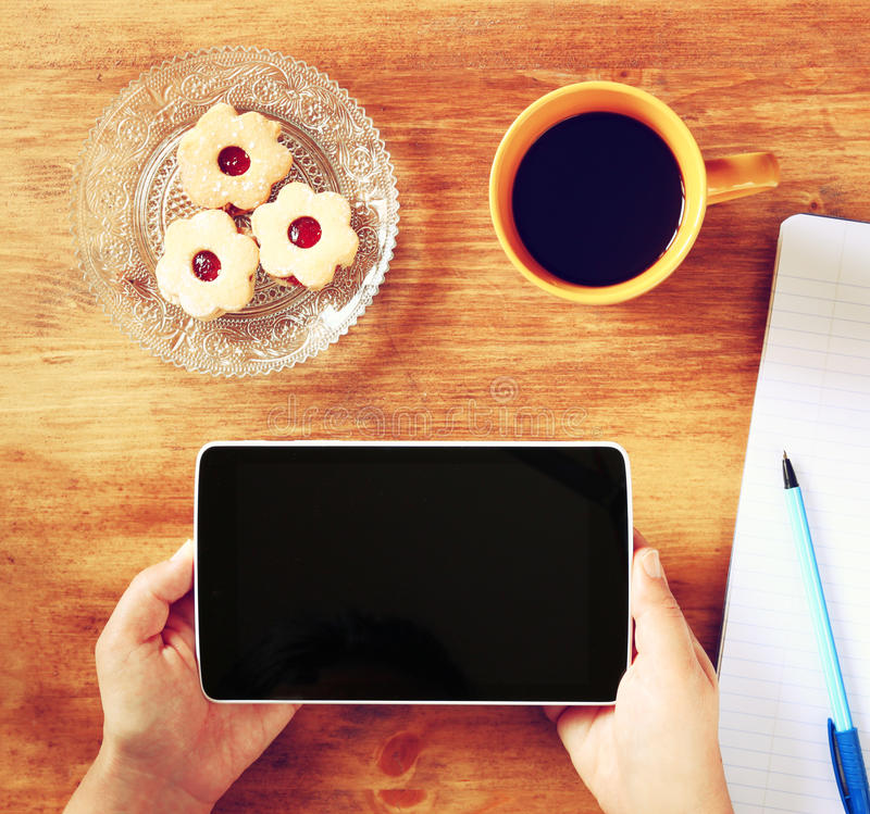Top view of woman hands holding tablet device with empty screen, with cookies and coffee cup. image is retro filtered royalty free stock photography