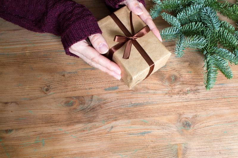 Top view of woman hands with simple gift box and christmas fir tree on wooden background. With free space royalty free stock photos