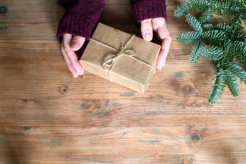 Top view of woman hands with simple gift box and christmas fir tree on wooden background. With free space royalty free stock photography