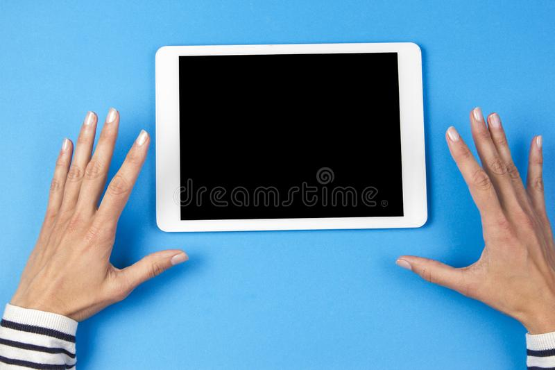Top view of woman hands with tablet computer on blue background royalty free stock photo