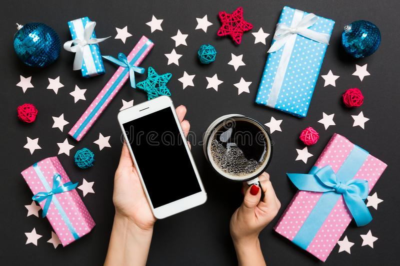 Top view of a woman holding a phone in one hand and a cup of coffee in another hand on black background. Christmas decorations and stock photo