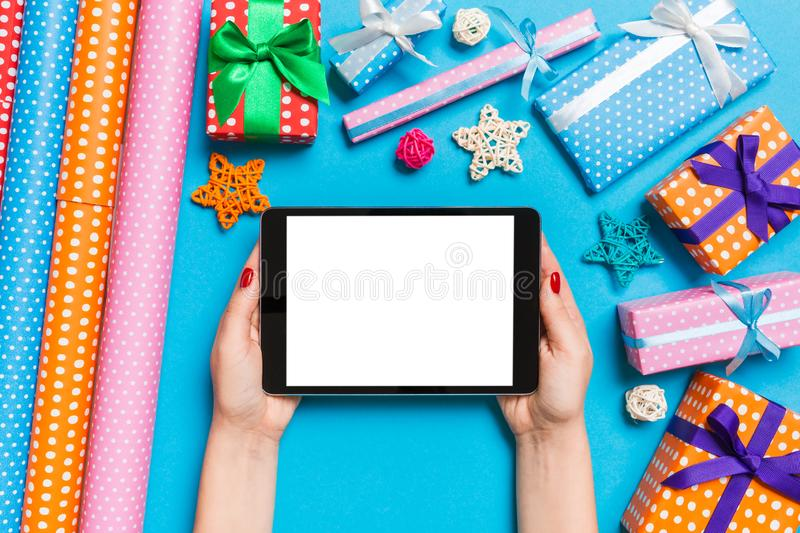 Top view of woman holding tablet in her hands on blue background made of Christmas decorations. New Year holiday concept. Mockup royalty free stock photo
