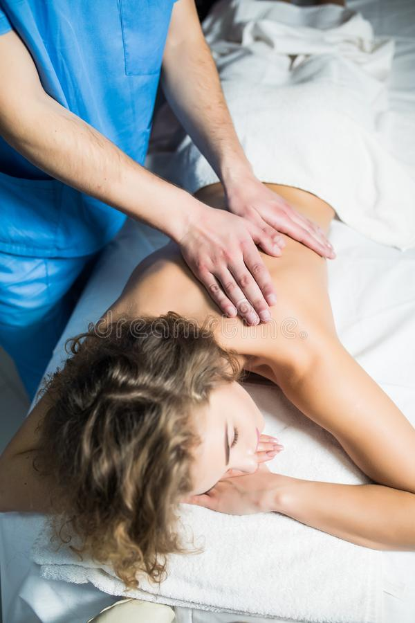 Top view of woman receiving back massage at spa. Female having relaxing massage on her back in spa. stock photography