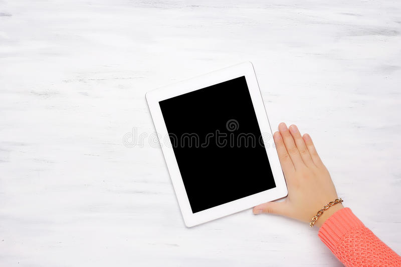 Top view of woman's hand holding tablet gadget on wooden table. stock photo