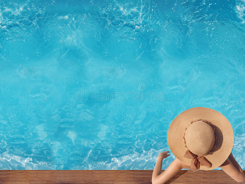 Top view of woman in straw hat relaxing in swimming pool at luxury villa resort. Summer holiday idyllic background. Vacations Con stock images