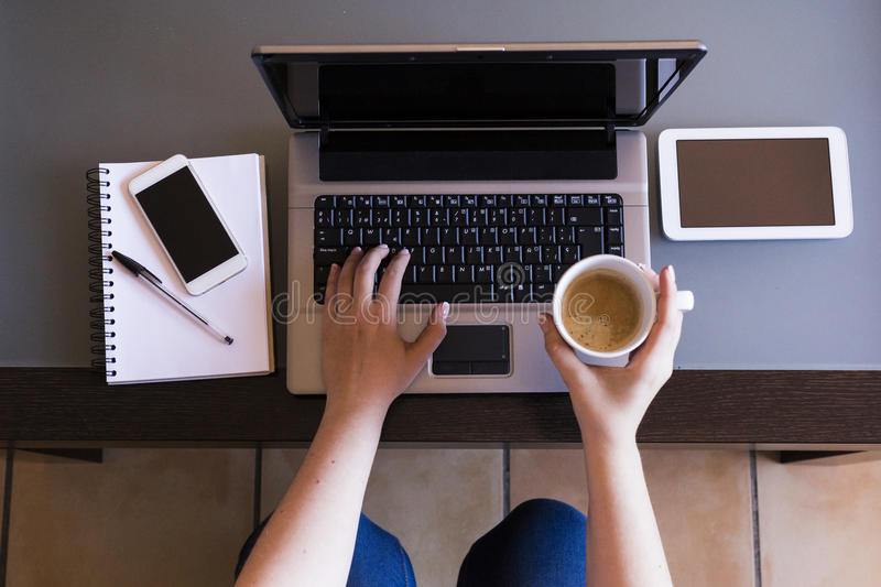 Top view of woman working on laptop with cup of coffee, smartphone, tablet and notebook. Indoors. Work space stock image
