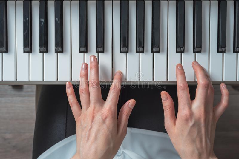 Top view of women`s hands playing the synthesizer, composing music.  royalty free stock photos