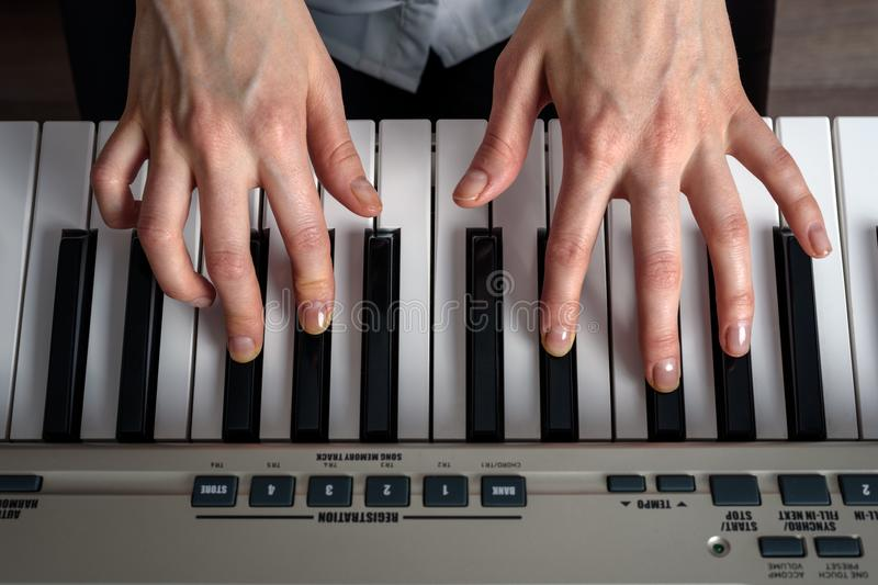 Top view of women`s hands playing the synthesizer, composing music. Top view of women`s hands playing the synthesizer, composing music royalty free stock photo