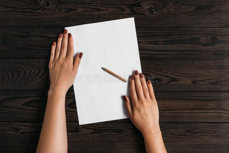 Top view of women`s hands, ready to write something on an empty piece of paper lying on a wooden table. White blank sheet of pape stock photography