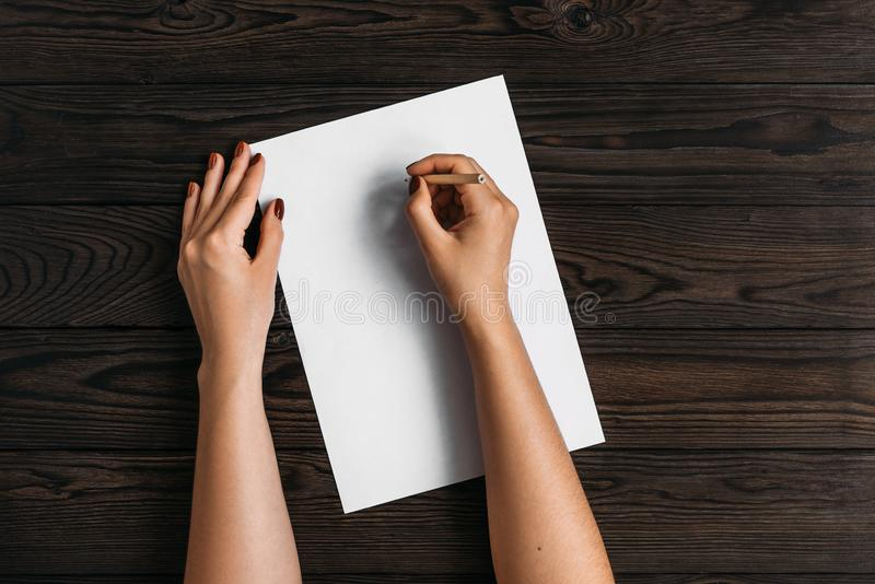 Top view of women`s hands, ready to write something on an empty piece of paper lying on a wooden table. White blank sheet of pape royalty free stock image