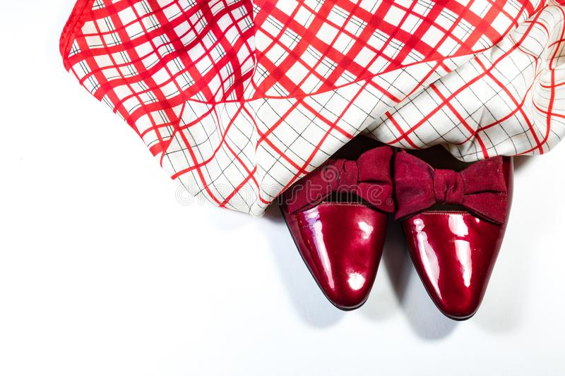 Top view of women`s vintage red shoes with bows with red and white plaid scarf, on white background. Copy space, horizontal aspect stock photography