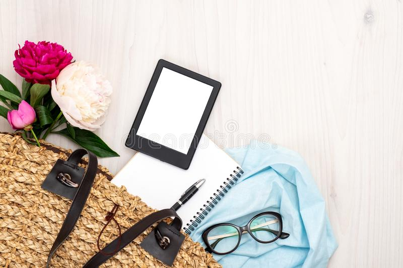 Top view women straw handbag with elegant feminine accessories: bouquet of peony flowers, e-book, blue cloth, paper notebook,. Glasses. Flat lay composition stock image