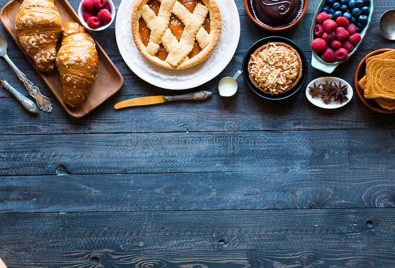 Top view of a wood table full of cakes, fruits, coffee, biscuits royalty free stock images