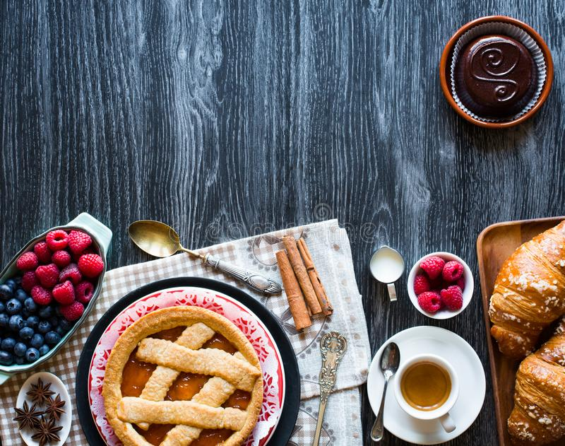 Top view of a wood table full of cakes, fruits, coffee, biscuits royalty free stock photography