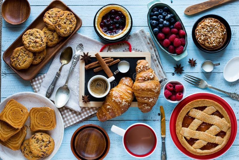 Top view of a wood table full of cakes, fruits, coffee, biscuits stock photo