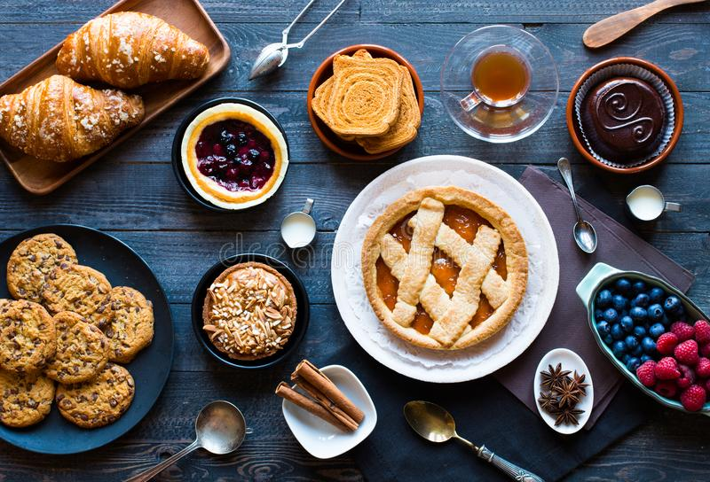 Top view of a wood table full of cakes, fruits, coffee, biscuits stock image