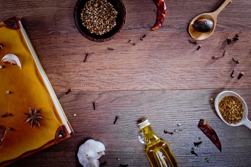 Top view on wooden background with spices, olive oil in bottle, garlic, papper chilli and note book. Backgrounds for the kitchen. Close-up royalty free stock photos