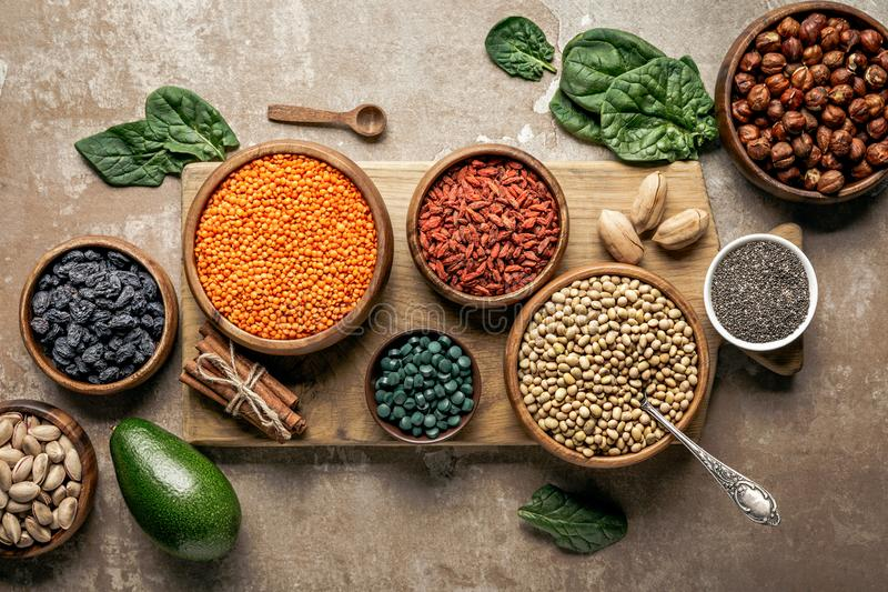 Top view of wooden board with legumes, goji berries and healthy ingredients. With rustic background stock images