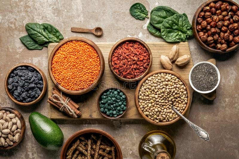 Top view of wooden board with legumes, goji berries and healthy ingredients. With rustic background royalty free stock photo