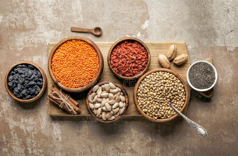 Top view of wooden board with legumes, goji berries and healthy ingredients. With rustic background royalty free stock photos