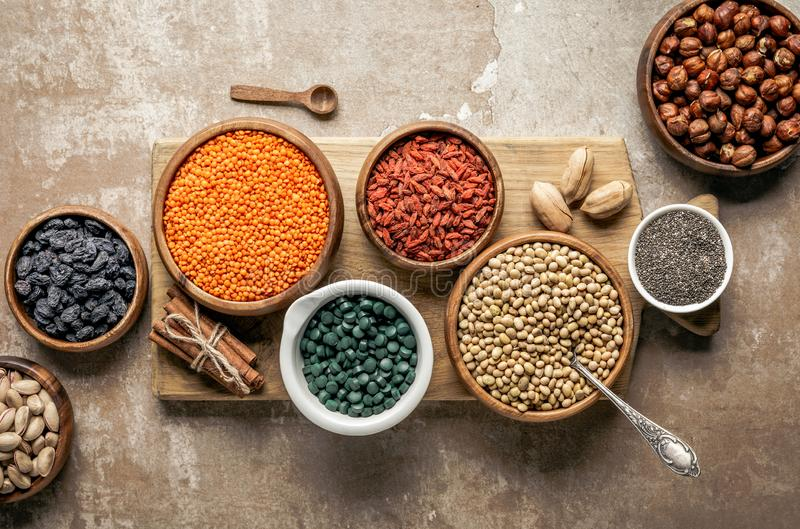 Top view of wooden board with legumes, goji berries and healthy ingredients. With rustic background stock photo
