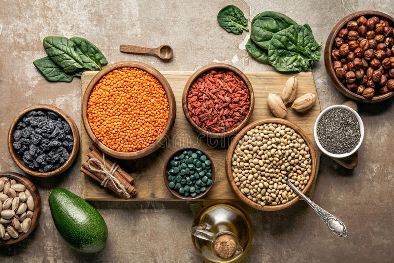 Top view of wooden board with legumes, goji berries and healthy ingredients. With rustic background stock photos