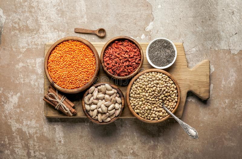 Top view of wooden board with legumes, goji berries and healthy ingredients. With rustic background royalty free stock photography
