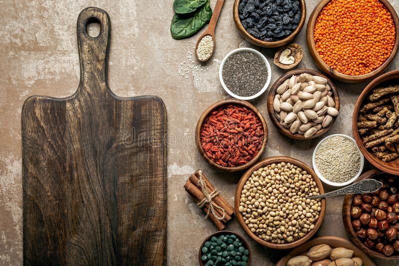 Top view of wooden board, superfoods, legumes and healthy ingredients. On rustic background stock images