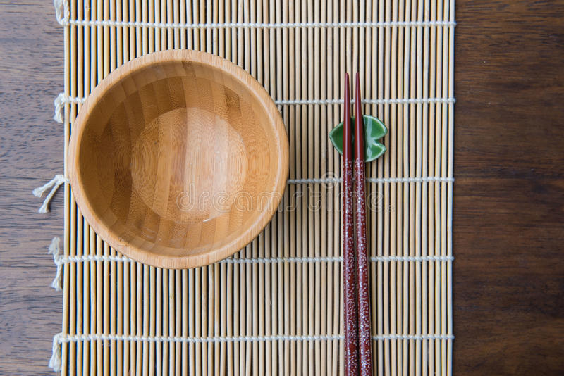 Top view Wooden bowl with chopsticks on bamboo mat on wooden table royalty free stock image