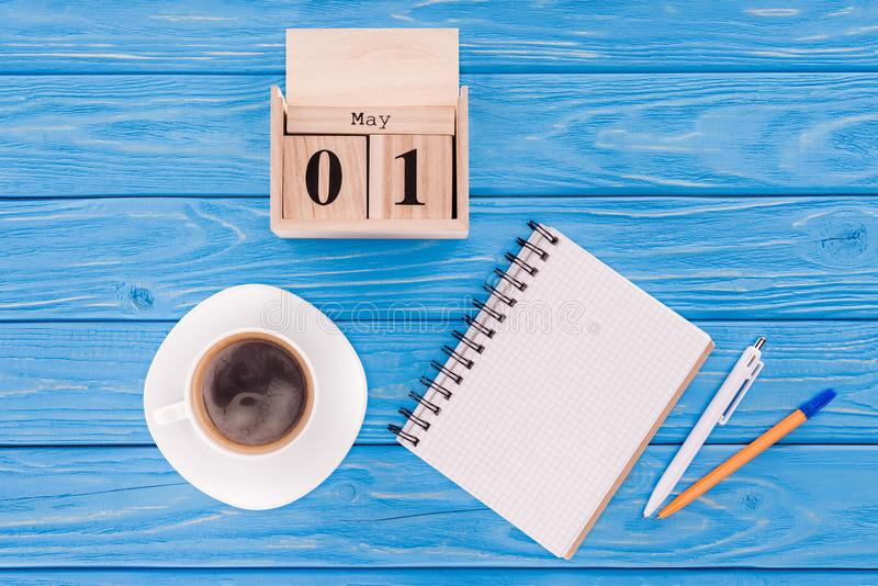 Top view of wooden calendar with date of 1st may, coffee cup, blank textbook and pens, international workers. Day concept stock image