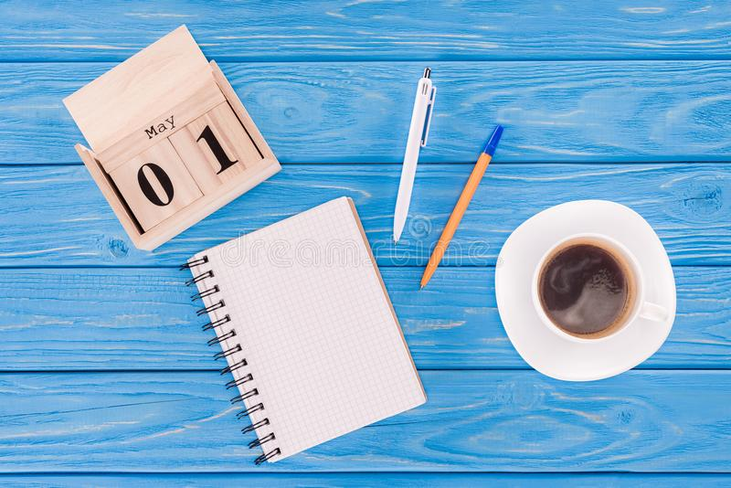 Top view of wooden calendar with date of 1st may, coffee cup, empty textbook and pens, international workers. Day concept stock image