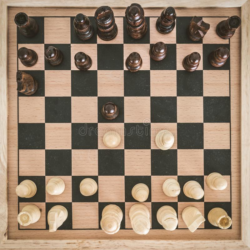 Top view on wooden chess board with chess figures ready for the game and man's hand making chess move on white wooden table. Top view on wooden chess board royalty free stock photos