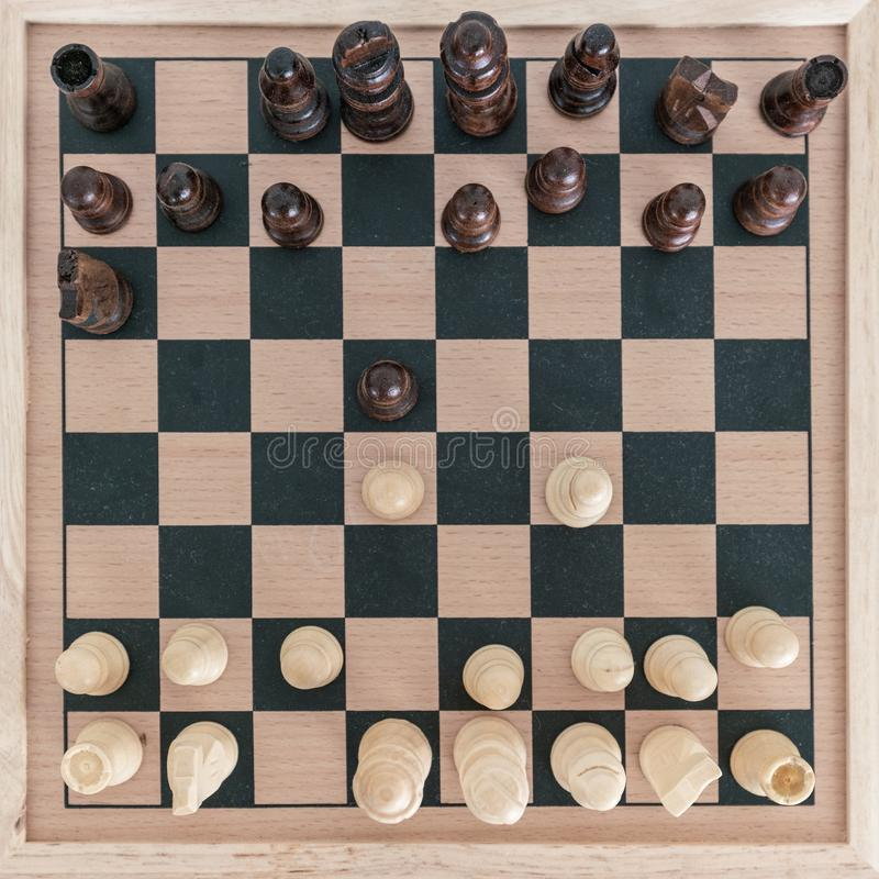 Top view on wooden chess board with chess figures ready for the game and man's hand making chess move on white wooden table. Top view on wooden chess board royalty free stock photo