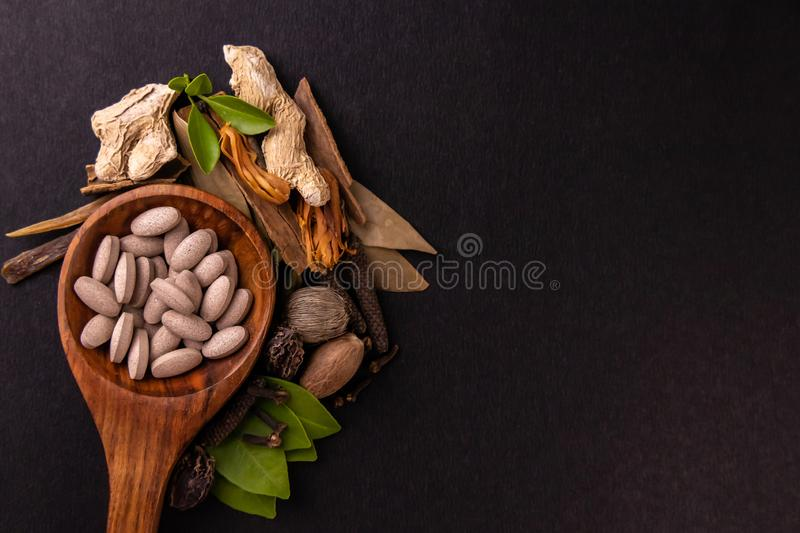 Top view of a wooden spatula containing brown herbal tablets with dry herbs and spices over black background. Herbal concept stock photos