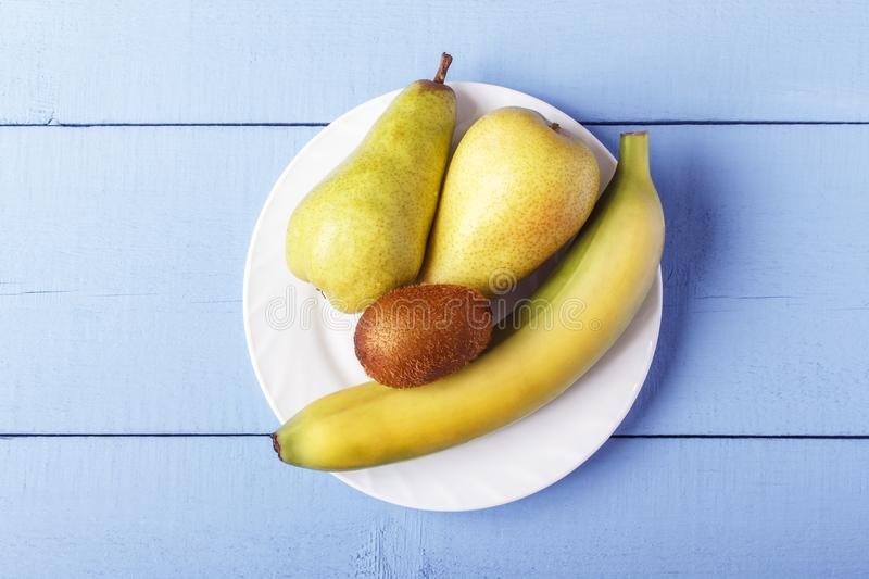 Top view on wooden table with heap fresh fruit. Pears, banana and kiwi fruit on white plate. Copy space stock image