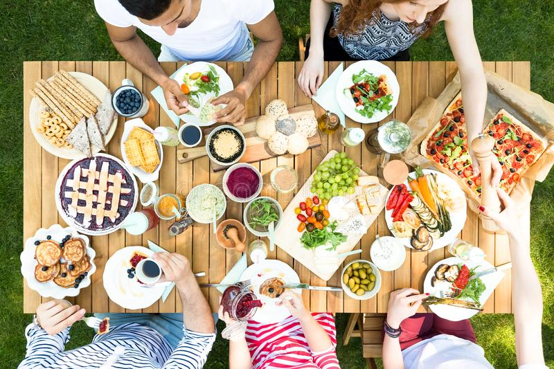 Top view on wooden table with pastry, pizza and fruit during gar. Den party royalty free stock images