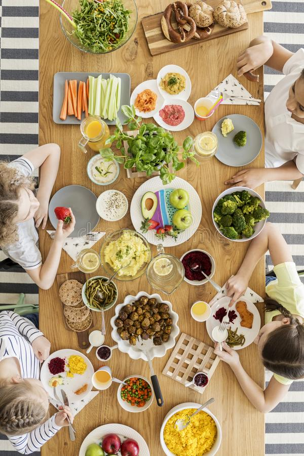 Top view of a wooden table with variety of fresh organic vegetables, fruit, salad and herbs. Kids eating delicious products. Top view of a wooden table with stock images