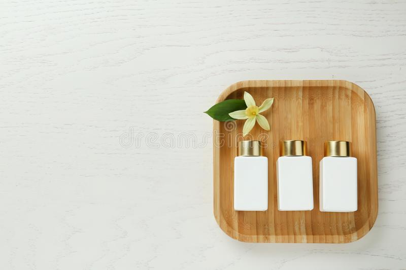 Top view of wooden tray with cosmetic bottles and flower on white table. Spa treatment. Top view of wooden tray with cosmetic bottles and flower on white table royalty free stock photos